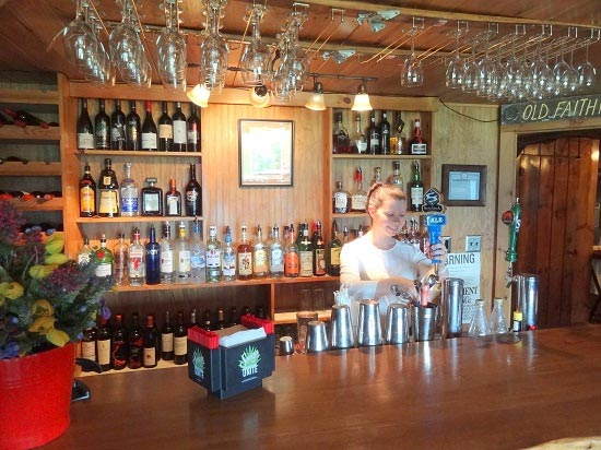 Bartenders pours draft beer at The Log House Pub at Garnet Hill Lodge