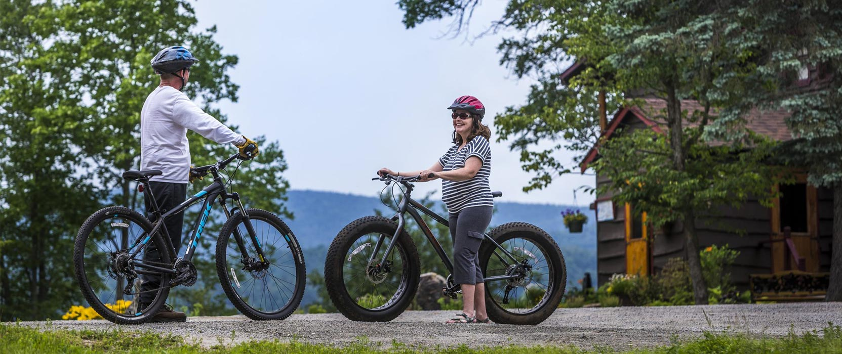 Two people holding mountain bikes with Garnet Hill Lodge in the background