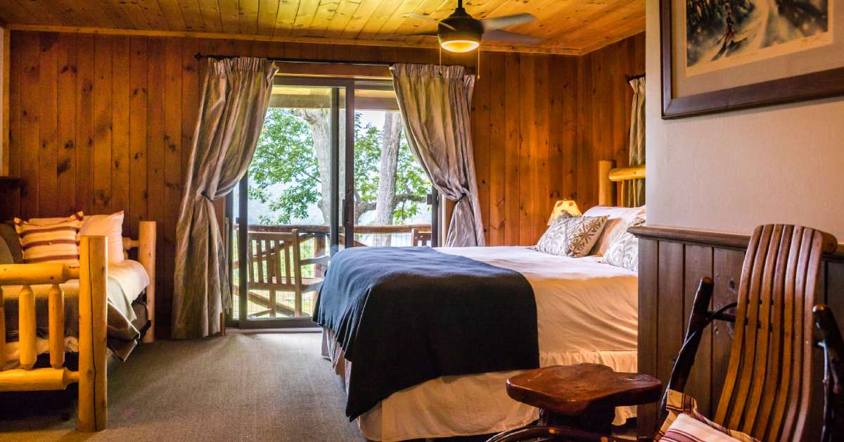 rustic bedroom with bed and view of the outdoors from balcony