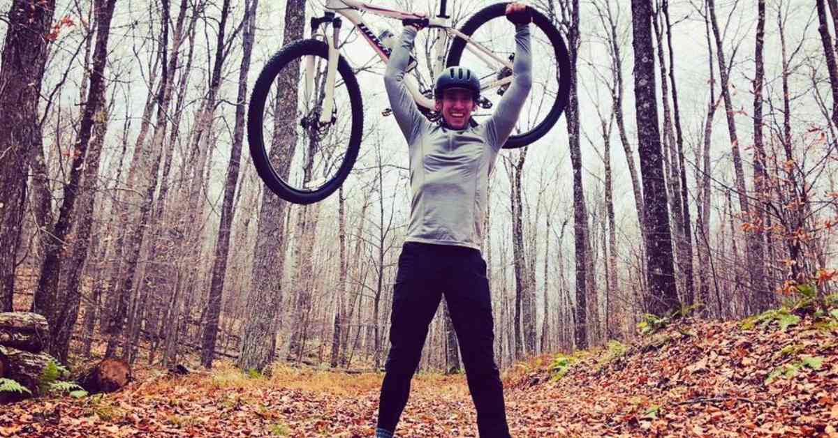 man holding up a mountain bike in the woods