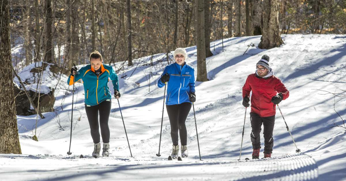 three cross country skiers moving uphill