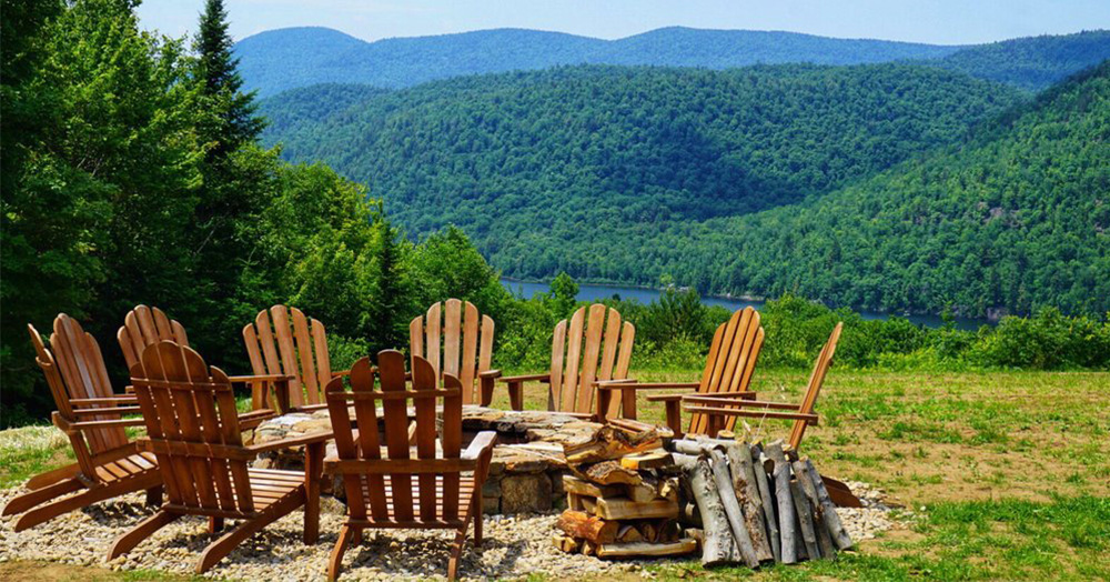 fire pit with adirondack chairs and a lake and mountain view in the background
