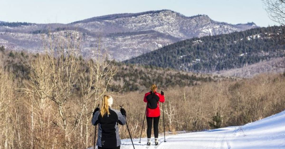two women skiing, mountain in front of them